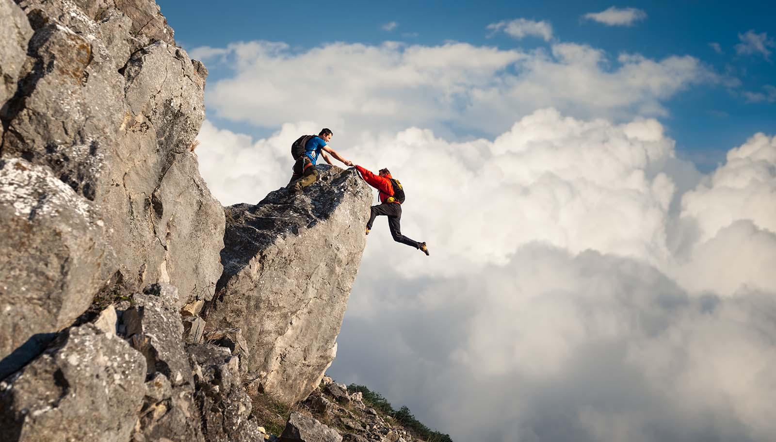 helping friend rock climb